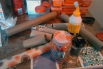 Stuff you need: craft glue, empty toilet paper rolls, array of scrap paper, ribbon, stiff board like from a box, glue gun